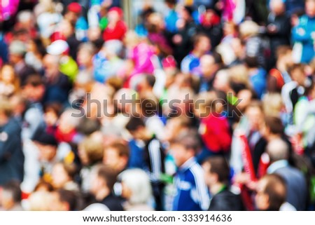 out of focus picture of a crowd of spectators at a street event