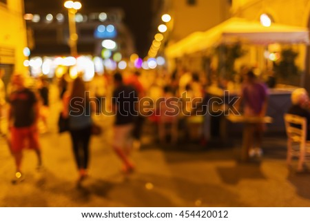 out of focus picture of a night scene with people and street restaurants in the old town of Florence, Italy - stock photo