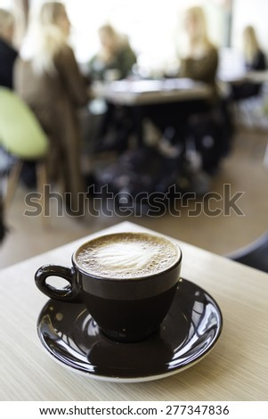 Out of focus shot of a cafe, with a cup of cappuccino in the foreground, - stock photo