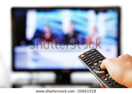 Out of focus TV LCD set and remote control in man's hand isolated over a white background. - stock photo
