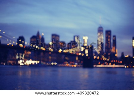 Out of focus view of Brooklyn Bridge at sunset, Downtown Manhattan, New York.Night scene. Light trails. City lights. Urban living and transportation concept - stock photo