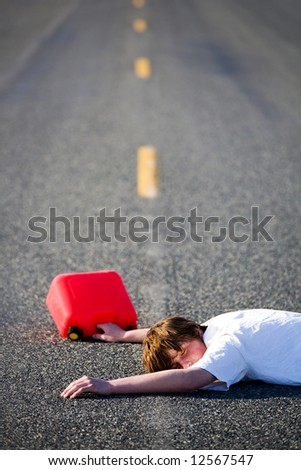 out of gas - teen with empty gas can lies dead in the middle of the road - stock photo
