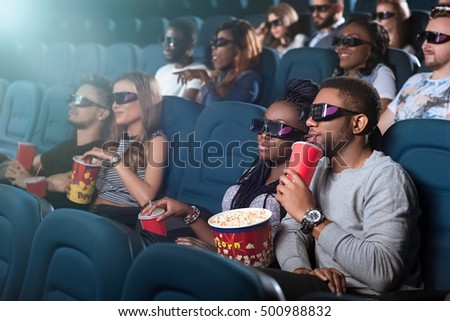 Out to the movies. Shot of a beautiful young couple having a date at the cinema watching a movie together wearing 3D glasses