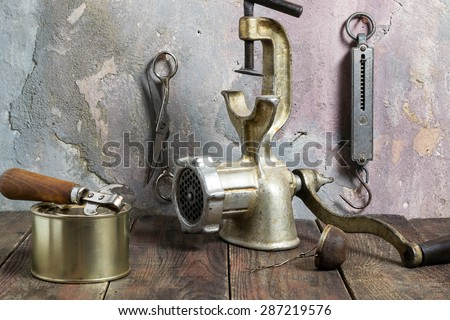 Outdated items Kitchen steelyard, scissors, manual grinder, tea strainer, can, can opener on a wooden table against a wall with an old plaster. Photo of vintage style - stock photo