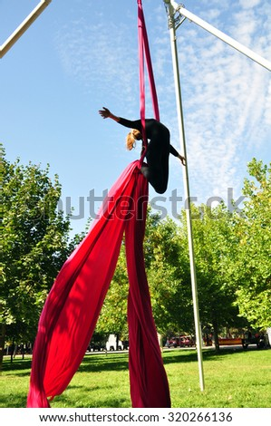 Outdoor activity of cheerful child training on aerial silks or ribbons. Childhood, sports, active lifestyle concept. - stock photo
