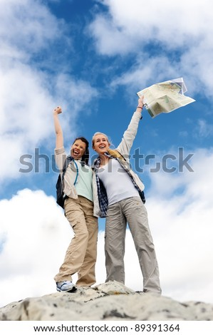 outdoor adventure woman are happy to be at the top of a mountain with map in hand - stock photo