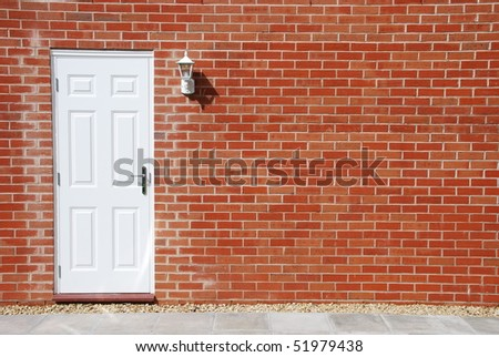 outdoor architecture with white door on a vibrant red brick wall - stock photo