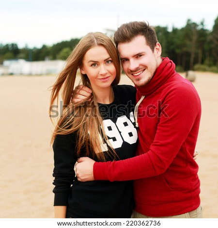 Outdoor autumn portrait of pretty nice young family couple in love posing on the beach smiling and having fun