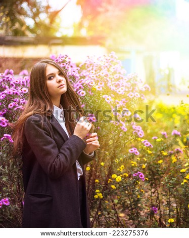 Outdoor autumn portrait of young pretty cute girl. Beautiful woman posing near flowerbed  - stock photo