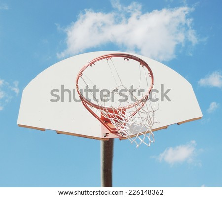 Outdoor basketball hoop with blue sky and clouds - stock photo