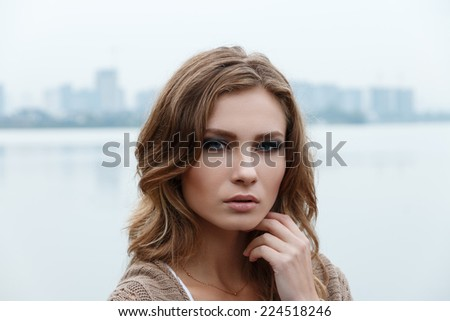 Outdoor beauty portrait of young blonde girl over city line background - stock photo