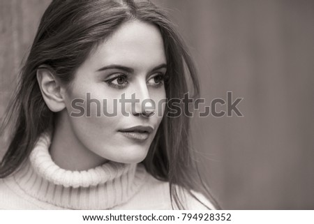 Outdoor black and white portrait of beautiful girl or young woman with wearing a white jumper