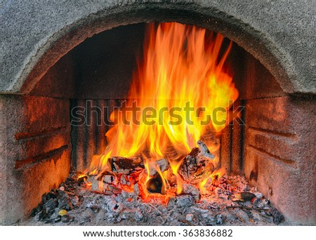 Outdoor brick fireplace with a fire blazing inside.