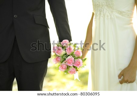Outdoor Bride and Groom holding flower bouquet