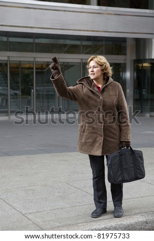 Outdoor business woman hailing a taxi cab - stock photo