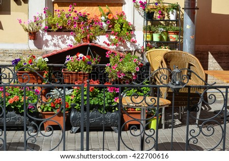 Outdoor cafe furniture. Table, armchairs. Summer terrace with flowers. - stock photo