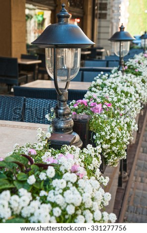 Outdoor cafe with beautiful lights and colorful floral baskets - stock photo