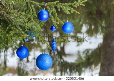 Outdoor Christmas azure shiny bauble ornaments are hanging on snowy spruce twig - stock photo