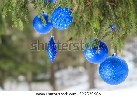 Outdoor Christmas blue textured bauble ornaments are hanging on snowy spruce twig - stock photo