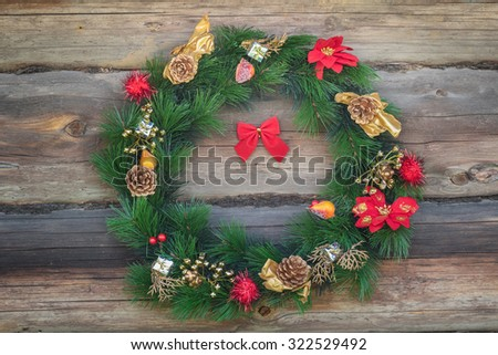 Outdoor Christmas conifer wreath at old grey log cabin wall background - stock photo