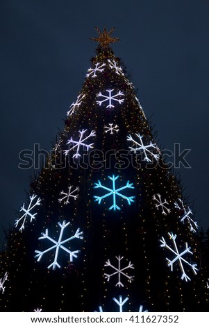 Outdoor Christmas tree decorated with light snowflakes  - stock photo