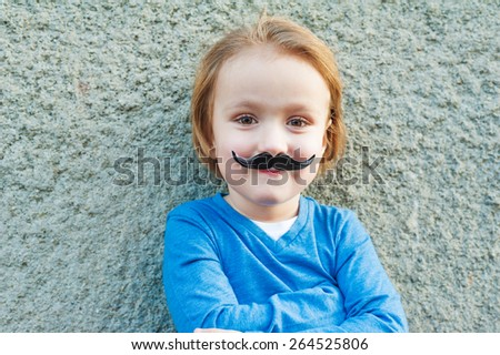 Outdoor close up portrait of a cute little boy with fake italian moustache - stock photo