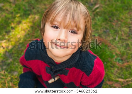 Outdoor close up portrait of adorable little blond boy of 4 years old with hairstyle and sweet smile on his face - stock photo