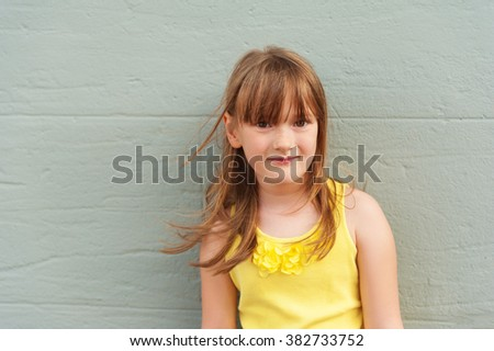Outdoor close up portrait of adorable little girl of 6-7 years old, wearing bright yellow top - stock photo