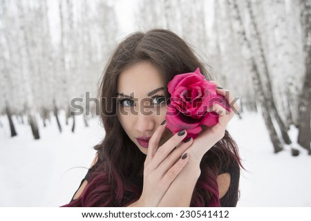 Outdoor Close up portrait of Young adult latin hispanic brunette Girl in winter cold december forest hold red rose in hand Cute woman wearing black dress on trees trunk and white snow drift background - stock photo