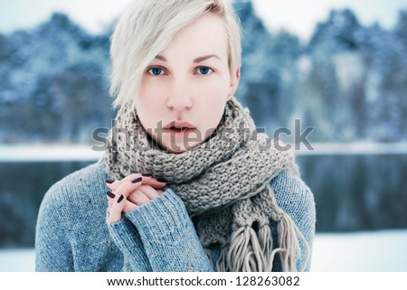 Outdoor closeup fashion portrait of young pretty sensual blonde with deep blue eyes in cold park