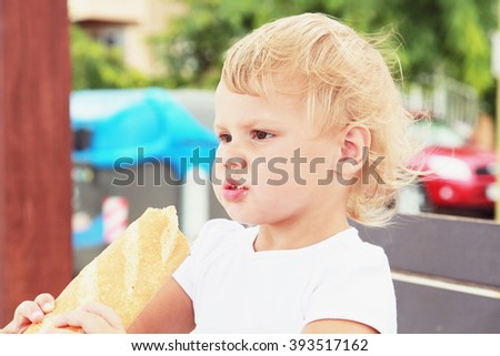 Outdoor closeup portrait of cute Caucasian blond baby girl eating big French baguette - stock photo