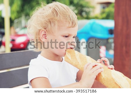 Outdoor closeup portrait of cute Caucasian blond baby girl eating French baguette - stock photo