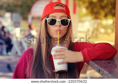 Outdoor closeup portrait of pretty stylish fashion girl having fun drinking chocolate milkshake in a cafe outdoors.  Lifestyle swag style photo with a vintage retro instagram filter - stock photo