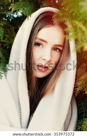 Outdoor closeup portrait of pretty young sensual smiling woman with closed eyes posing in park