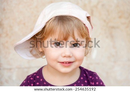 Outdoor closeup portrait of smiling cute Caucasian blond baby girl in white baseball cap - stock photo