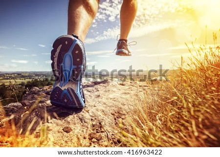 Outdoor cross-country running in summer sunshine concept for exercising, fitness and healthy lifestyle - stock photo