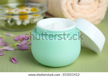 outdoor facial cream with chrysanthemum in the bowl  and towel on wooden background
