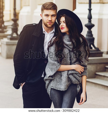 Outdoor fall portrait of fashionable pretty young couple wearing trendy monochrome outfit . Two lovers posing against theater background in autumn sunlight. - stock photo
