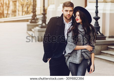 Outdoor fall portrait of fashionable pretty young couple wearing trendy  outfit . Two lovers posing against theater background in autumn sunlight. - stock photo
