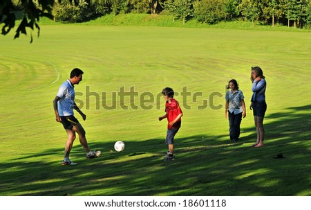 outdoor family group playing football - stock photo