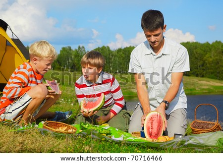 outdoor family portrait of two boys eating watermelon at the picnic. young man is cutting watermelon
