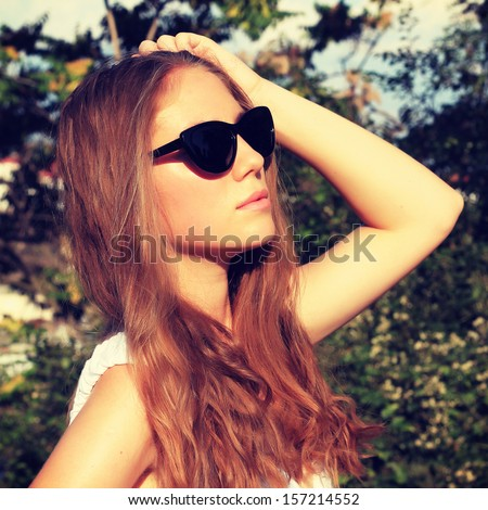 Outdoor fashion closeup portrait of young pretty woman on street - stock photo