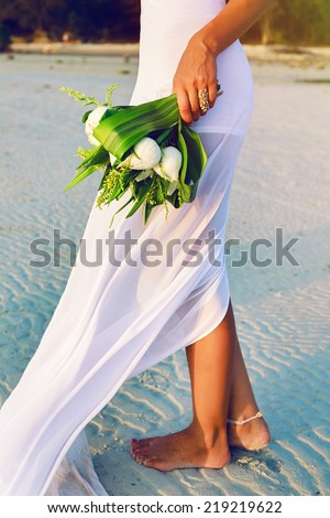 Outdoor fashion image of bride posing alone at exotic beach at sunset with beautiful wedding lotus bouquet, have nice simple trendy white dress. - stock photo