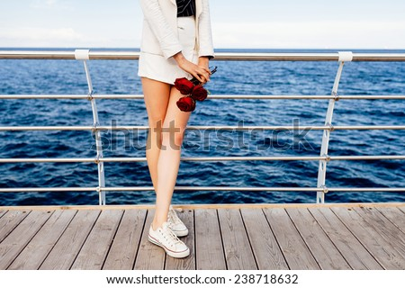 Outdoor fashion image of stylish woman with long sexy slim legs, wearing white suit casual keys and holding bouquet of red roses. Posing near blue deep navy sea. - stock photo