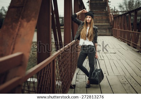 Outdoor fashion lifestyle portrait of pretty young girl, wearing in hipster swag grunge style urban background. Retro vintage toned image, film simulation. - stock photo
