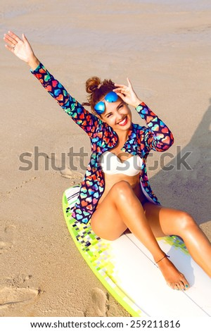 Outdoor fashion lifestyle summer portrait of stunning sexy surfer woman, wearing bright outfit makeup and sunglasses. Sitting on surf board smiling, put her hands in the air and enjoy her freedom. - stock photo