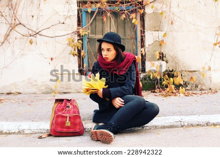 Outdoor fashion lifestyle urban portrait of young hipster woman traveling with backpack. Wearing black coat and hat. Photo toned style Instagram filters. - stock photo
