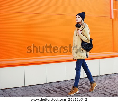 Outdoor fashion photo of stylish hipster cool girl walking in the city against a colorful urban wall - stock photo