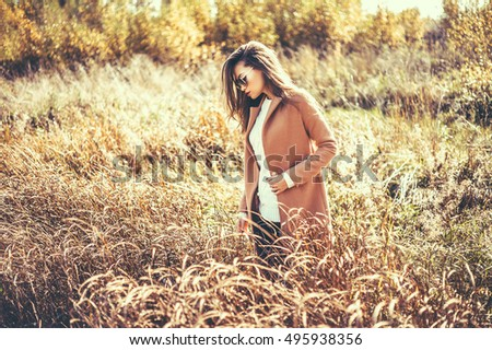 Outdoor fashion photo of young beautiful lady in autumn landscape with dry flowers. Autumn/Winter. Warm autumn/winter. Fashion autumn/winter. Beautiful autumn. Sunny autumn, Cozy autumn coat