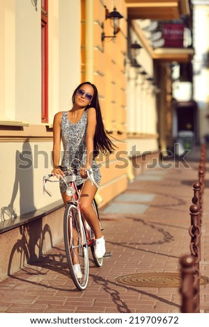 Outdoor fashion portrait of a beautiful brunette with bike - stock photo